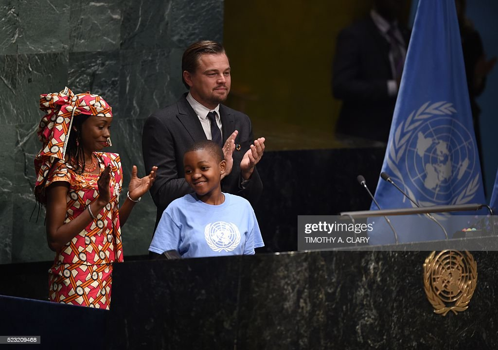Hindou Oumarou Ibrahim, Coordinator of the Indigenous Women and Peoples Association of Chad, Getrude Clement(C), Youth Representative from Tanzania, and Leonardo DiCaprio, actor and UN Messenger of Peace attend the high level signature ceremony for the Paris Agreement at the United Nations General Assembly Hall April 22, 2016 in New York. / AFP / TIMOTHY