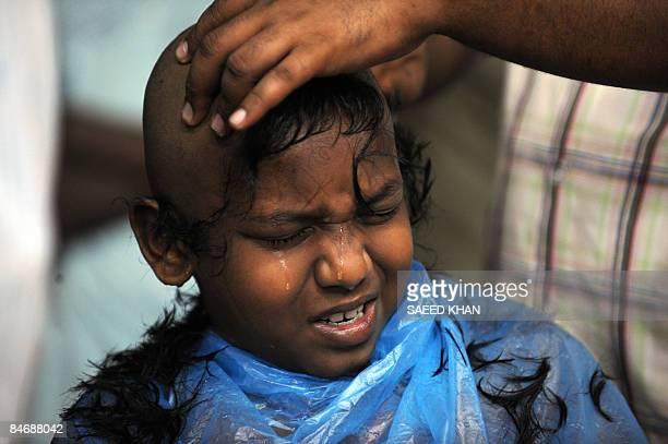 A Hindu boy cries while having a head shave at the Batu Caves temple at sunrise during Thaipusam in Kuala Lumpur on February 8 2009 The Hindu...