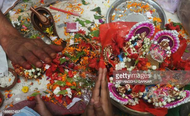 Hindu business men offer prayers with idols of Hindu gods Ganesha and Laxmi and new ledger books at Kalighat temple during the Bengali new year...