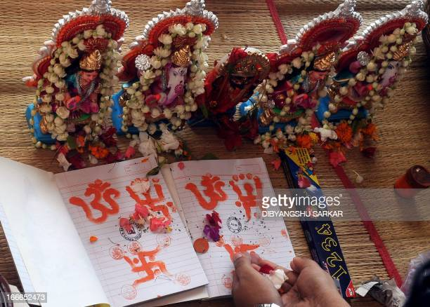 Hindu business men pray with idols of Hindu gods Ganesha and Laxmi and new ledger books at Kalighat temple during the Bengali new year celebrations...