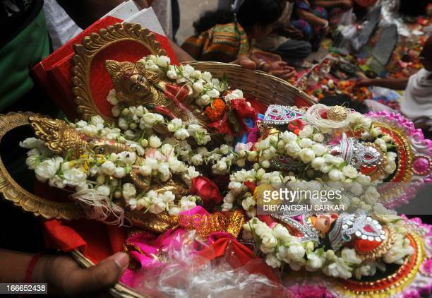 Hindu business men queue with idols of Hindu gods Ganesha and Laxmi and new ledger books in a traditional bamboo basket to offer prayers at Kalighat...