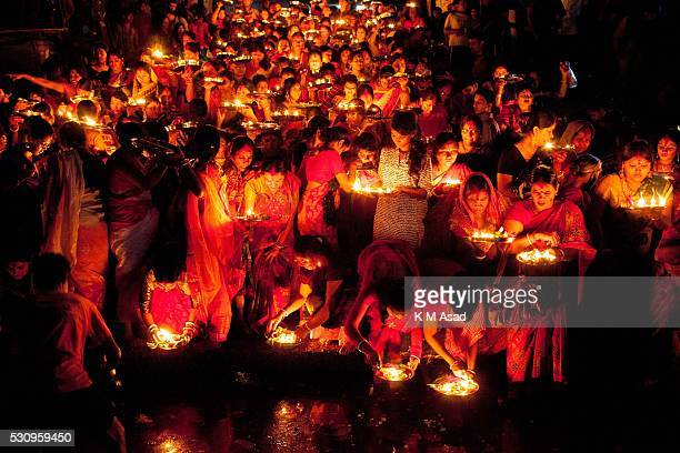Hindu community women with candlelight offering pooja to Bipadtarini Devi in Burigonga River near Dhaka Bangladesh July 25 2015 During the ritual of...