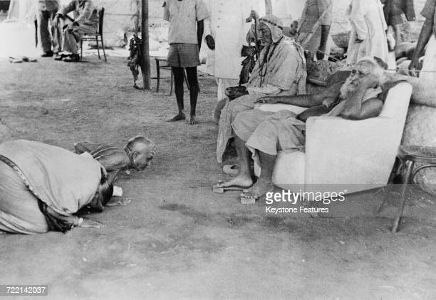 A Hindu couple prostrate themselves before a swami at a ceremony of prayer for world peace in Mumbai India February 1947 The worshippers have...