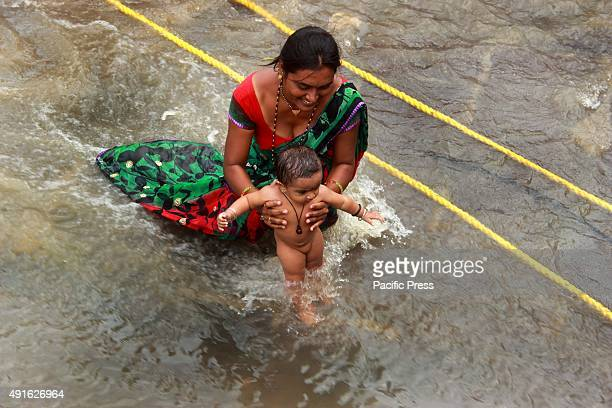 Hindu devotee bathing her baby during the holy bath in Godavari river The major event of the Kumbh Mela festival is the ritual bathing at the rivers...
