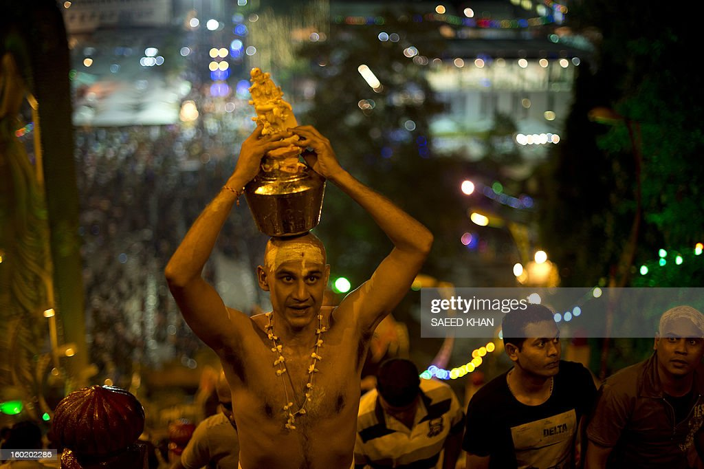 A Hindu devotee carries a milk pot on his head for offering during the Thaipusam Festival at the Batu Caves on the outskirts of Kuala Lumpur on January 28, 2013. The Hindu festival of Thaipusam, which commemorates the day when Goddess Pavarthi gave her son Lord Muruga an invincible lance with which he destroyed evil demons, is celebrated by some two million ethnic Indians in Malaysia and Singapore. AFP PHOTO / Saeed KHAN