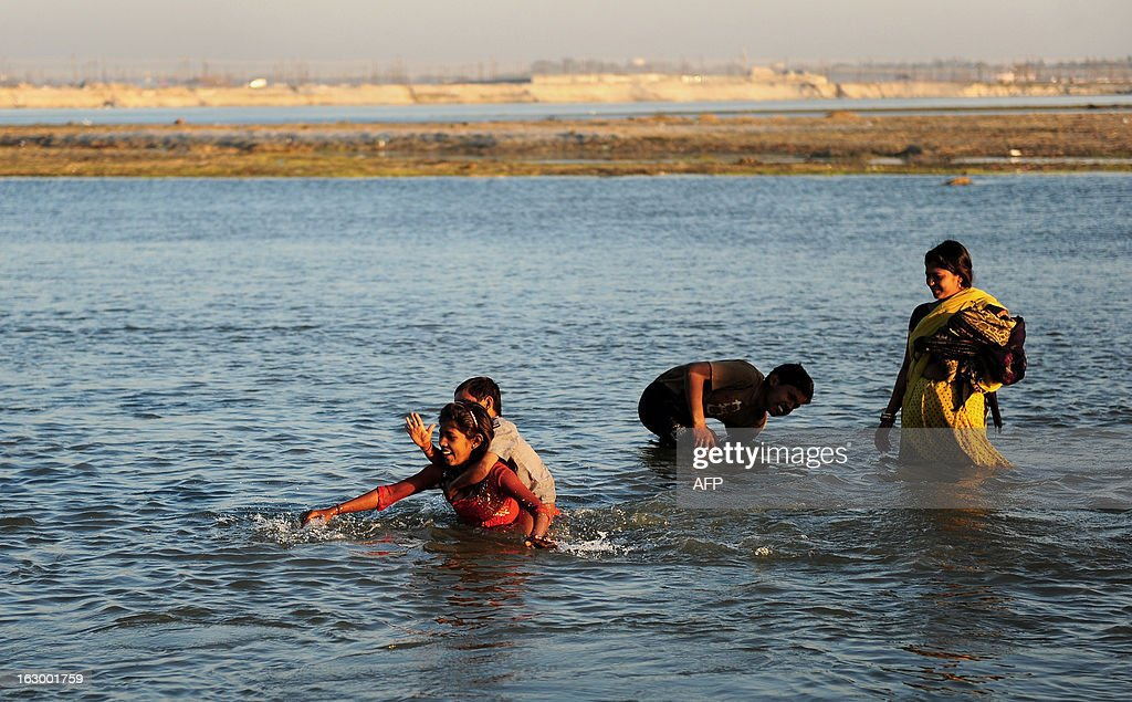 A Hindu devotee carries a young boy across the Ganga River after rains caused the water levels to rise in the Kumbh Mela area in Allahabad on March 3, 2013. The Kumbh Mela in the town of Allahabad sees up to 100 million worshippers gather over 55 days to take a ritual bath in the holy waters, believed to cleanse sins and bestow blessings. AFP PHOTO/Sanjay KANOJIA