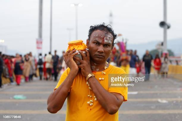 Hindu devotee carries pot of milk on his shoulder prior to walking up to the Batu Caves Temple during the festival of Thaipusam in Kuala Lumpur...