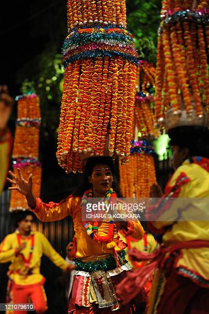 Hindu devotee dancers perform in front of the historic Buddhist Temple of the Tooth, as they take part in a procession during the Esala Perahera...