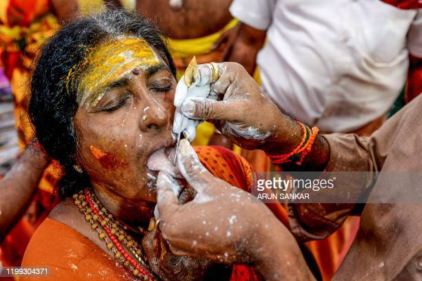 Hindu devotee gets the tongue pierced with metal skewers while taking part in a procession during the Thaipoosam festival in Chennai on February 8,...