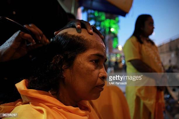 Hindu devotee has her head shaved before making her way towards the Batu Caves temple during the Thaipusam Hindu festival on January 29 2010 in Batu...