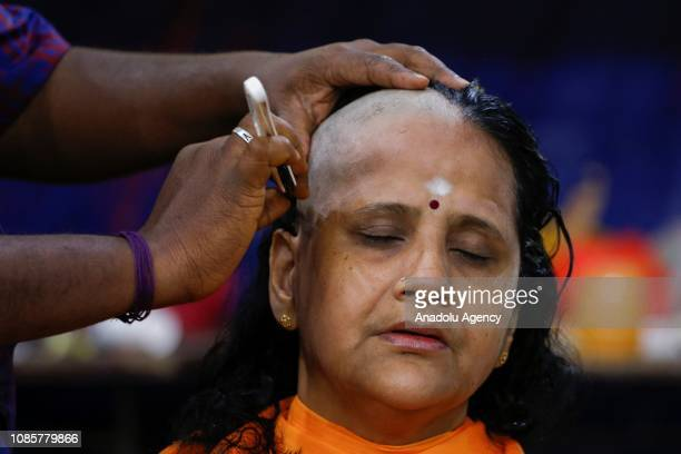 Hindu devotee has her head shaved in a ritual held prior to walking up to the Batu Caves Temple during the festival of Thaipusam in Kuala Lumpur...
