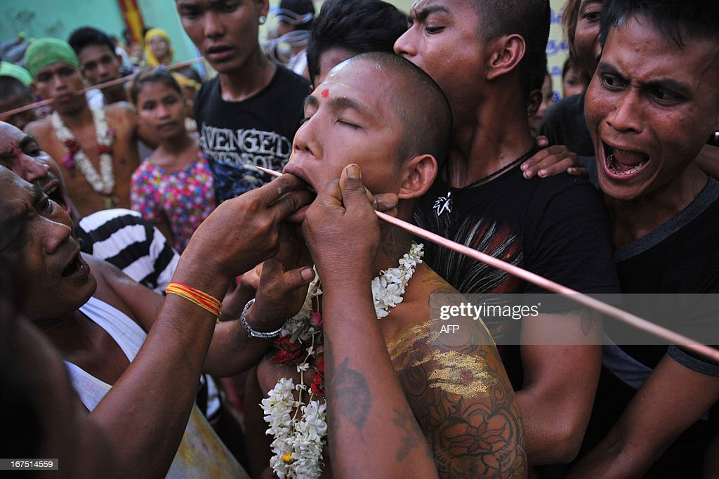 Hindu devotee (C) has his body pierced during a Hindu festival in Yangon on 25th April 2013. Although only an estimated two per cent of Myanmar's population practice Hinduism in this majority Buddhist country, most of them being Myanmar Indians, Hindu influences can be found in the Myanmar language, culture and the architecture of cities such as Bagan.