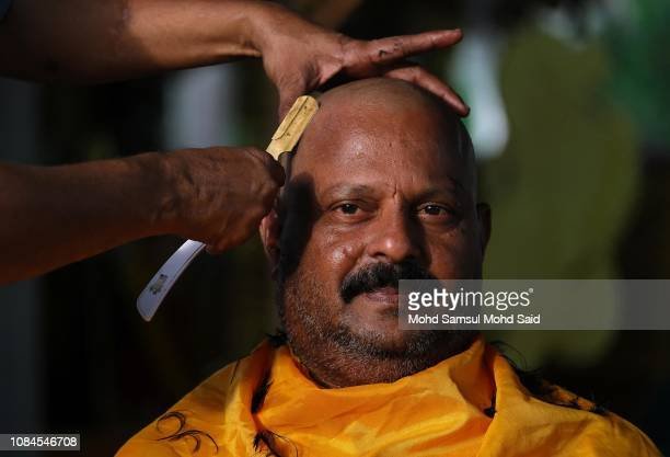 Hindu devotee has his head shaved before his pilgrimage to the sacred Batu Caves temple during the Thaipusam festival on January 18 2019 outside...