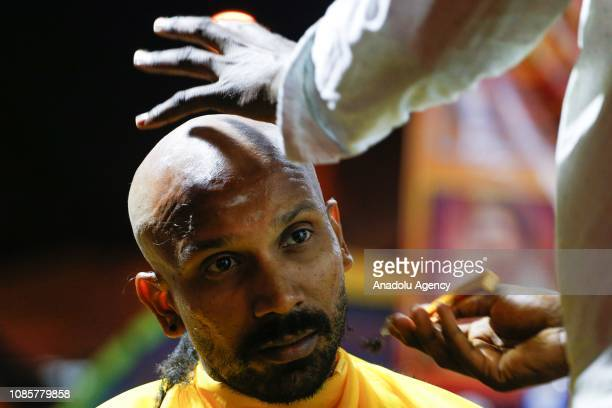 Hindu devotee has his head shaved in a ritual held prior to walking up to the Batu Caves Temple during the festival of Thaipusam in Kuala Lumpur...