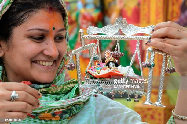 """Hindu devotee holds an idol of Hindu deity Lord Krishna on the occasion of the """"Janmashtami"""" festival that marks Krishna's birthday, at a temple in..."""
