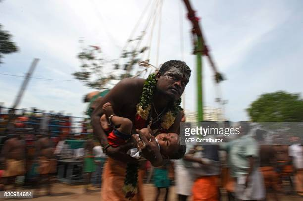 Hindu devotee holds his child while hanging with hooks pierced to his back during a ritual on the occasion of 'Aadi' festival in Chennai on August 13...
