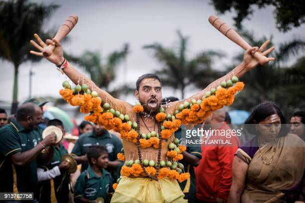 A Hindu devotee hooked with spikes lime coconutsfruits and flowers to his mouth and body gestures takes part in the annual Hindu Thaipoosam Kavady...