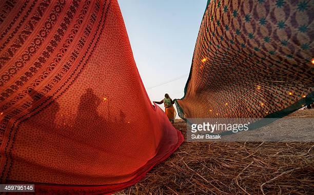 Hindu devotee is drying sari after having bathed on the banks of Sangam the confluence of the holy rivers Ganges Yamuna and the mythical Saraswati...