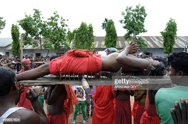 A Hindu devotee lies on a bed of nails as he is carried past spectators during the ritual of Shiva Gajan at Pratapgarh village in Agartala the...