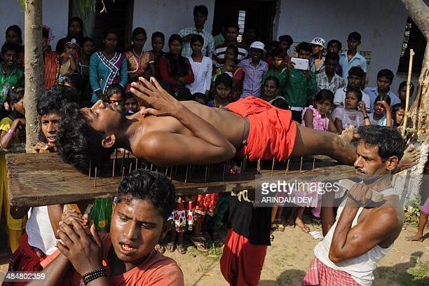 A Hindu devotee lies on a bed of nails while fellow mates carry him past spectators during the ritual of Shiva Gajan at Pratapgarh village in...