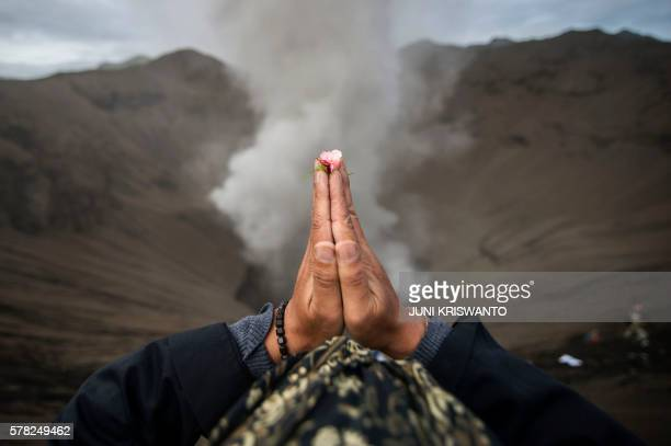 Hindu devotee of the Tengger tribe prays during the Yadnya Kasada festival on the crater of Mount Bromo in Probolinggo on July 21 2016 During the...