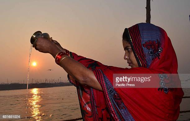 Hindu devotee offer prayer during Sunrise at Sangam after taking holy dip on the occasion of Makar Sankranti festival in Allahabad