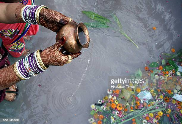 Hindu devotee offering water to the rising sun standing in water on the occasion of Chhat Festival on October 30 2014 in Indore India Chhath puja is...
