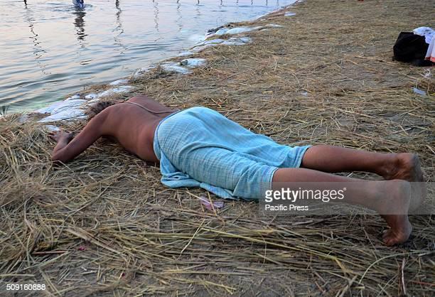 Hindu devotee offers evening prayer before taking holy dip in Sangam the confluence of River Ganga Yamuna and Mythological Saraswati during Magh mela...