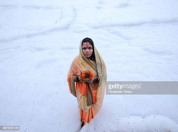 Hindu devotee offers prayers to setting sun during the Chhath festival on the banks of river Yamuna on November 17 2015 in Noida India Chhath...