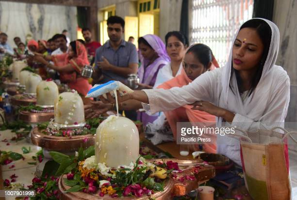 Hindu devotee performing Abhishek to Lord Shiva as they offer prayer at a temple on the 1st monday of Shrawan Month