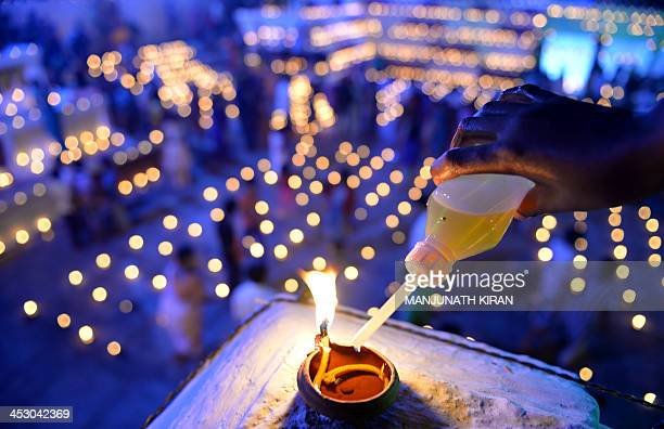 A Hindu devotee pours oil into a wick lamp at a temple for the Hindu God Shiva during the Karthigai Deepam in Bangalore on December 2 2013 Karthigai...