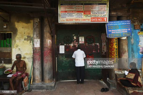 Hindu devotee prays outside the closed main entrance gste of the Kalighat Temple on the occassion of Bengali New Year during a government-imposed...