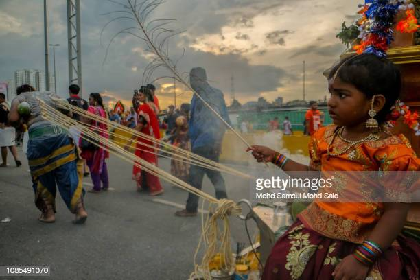 Hindu devotee pulls a chariot with ropes tied to piercings in his back during a pilgrimage to the sacred Batu Caves temple during Thaipusam festivals...