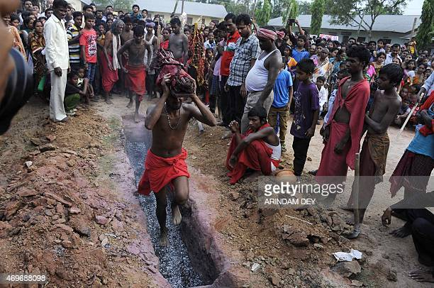 A Hindu devotee runs over smouldering charcoal during the ritual of Shiva Gajan at Pratapgarh village in Agartala the capital of northeastern state...