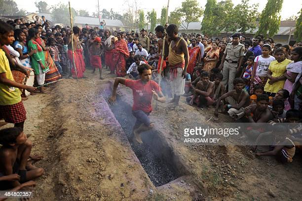 A Hindu devotee runs over smouldering charcoal during the ritual of Shiva Gajan at Pratapgarh village in Agartala the capital of northeastern Indian...