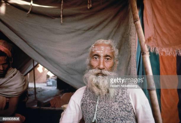 Hindu devotee sits near a tent of a Hindu holy man January 1 1989 at the Kumbh Mela religious festival in Allahabad India The Kumbh Mela a spiritual...