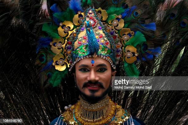 Hindu devotee smiles while wearing a headdress near the river before his pilgrimage to the sacred Batu Caves temple during the Thaipusam festival on...