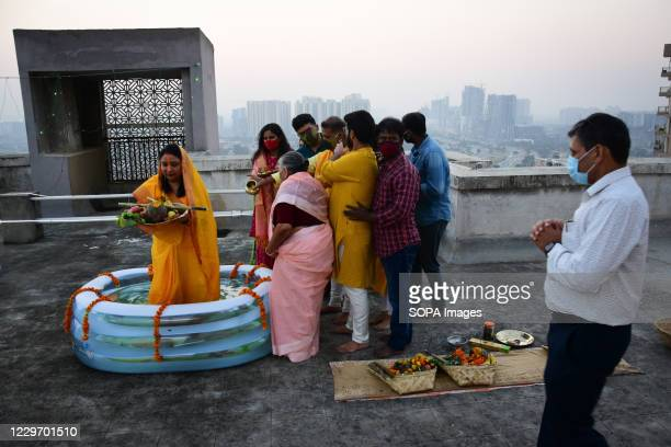 Hindu devotee stands inside a bath tub full of water as she performs rituals during the Chhath festival at the roof top. Chhath Puja is dedicated to...