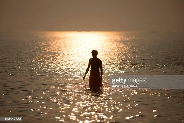 A Hindu devotee takes a holy dip in the Bay of Bengal during the Gangasagar Mela at Sagar Island around 150 kms south of Kolkata on January 13 2020...