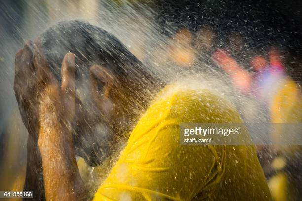 A Hindu devotee takes a shower during Thaipusam festival to fulfil their vows and offer thanks to the deities.