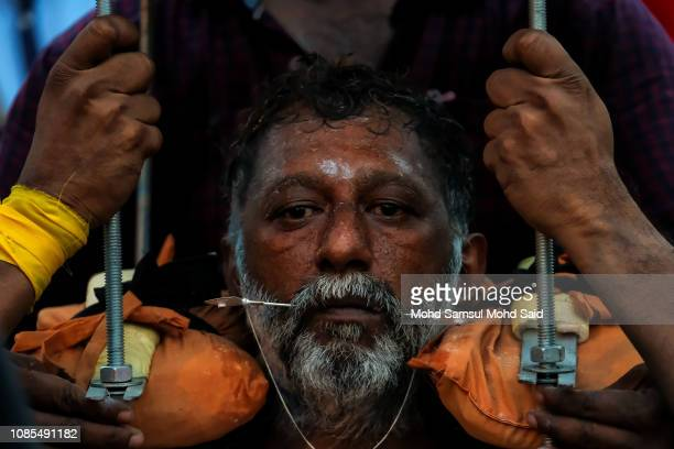 Hindu devotee with a piercing through his mouth carries a kavadi on his body before his pilgrimage to the sacred Batu Caves temple during Thaipusam...