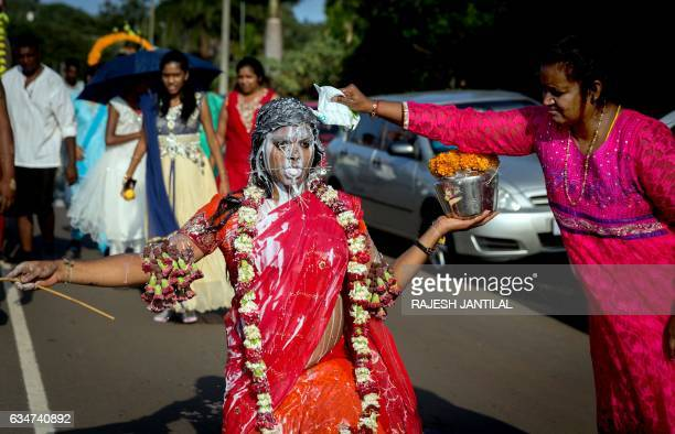Hindu devotee with her body pierced with spikes and flowers gestures as milk is poured on her during the annual Hindu Thaipusam Kavady on February...