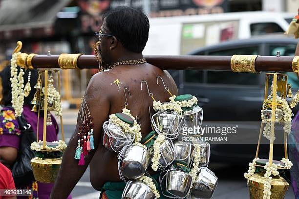 Hindu devotee with ornamental facial and body piercings carries offerings of milk along a procession route in Singapore's Little India district as...