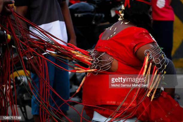 A Hindu devotee with piercings through his body as she perform a prayer at Batu Caves temple during Thaipusam festivals on January 21 2019 outside...