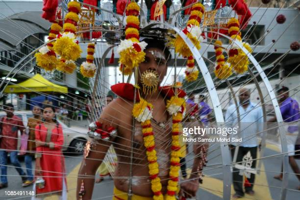 Hindu devotee with piercings through his body carries a kavadi on his body for his pilgrimage to the sacred Batu Caves temple during Thaipusam...