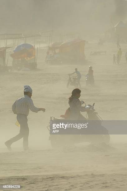 Hindu devotees are pictured in a dust storm at the Sangam the confluence of the rivers Ganges Yamuna and mythical Saraswati in Allahabad on April 5...