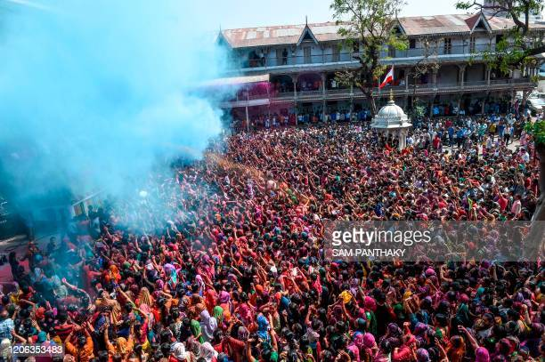 Hindu devotees are sprayed with coloured water as they celebrate Holi the spring festival of colours at Kalupur Swaminarayan temple in Ahmedabad on...