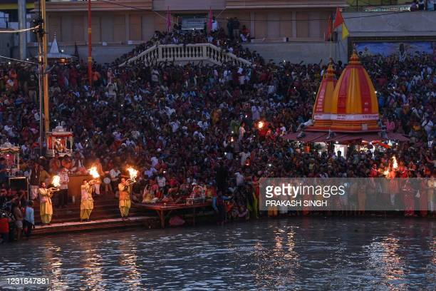 Hindu devotees attend evening prayers after taking a holy dip in the waters of the River Ganges on the Shahi Snan on the occasion of the Maha...