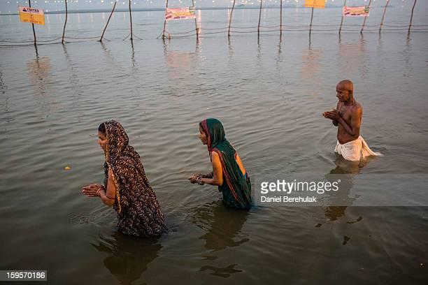 Hindu devotees bathe on the banks of Sangam the confluence of the holy rivers Ganges Yamuna and the mythical Saraswati during the Maha Kumbh Mela on...