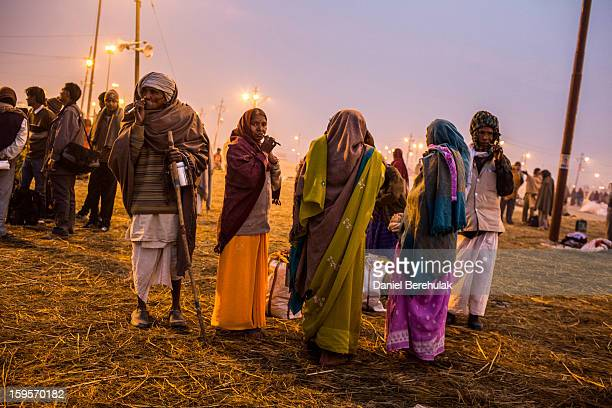 Hindu devotees brush their teeth with neem sticks prior to their bath on the banks of Sangam the confluence of the holy rivers Ganges Yamuna and the...